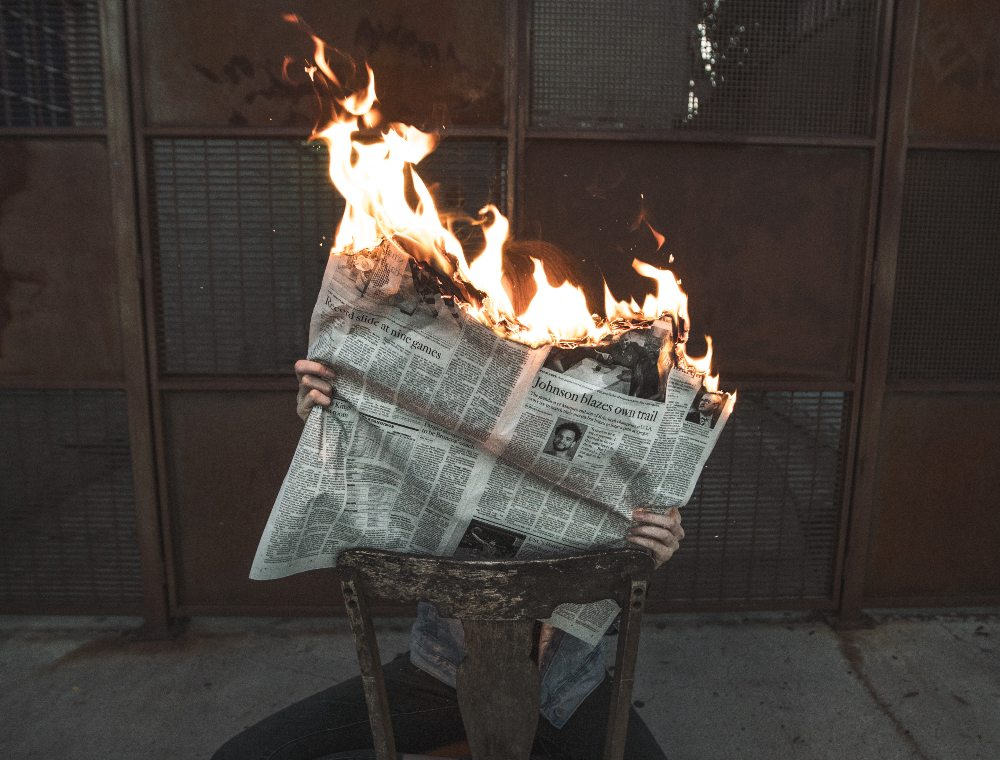 reading newspaper on fire